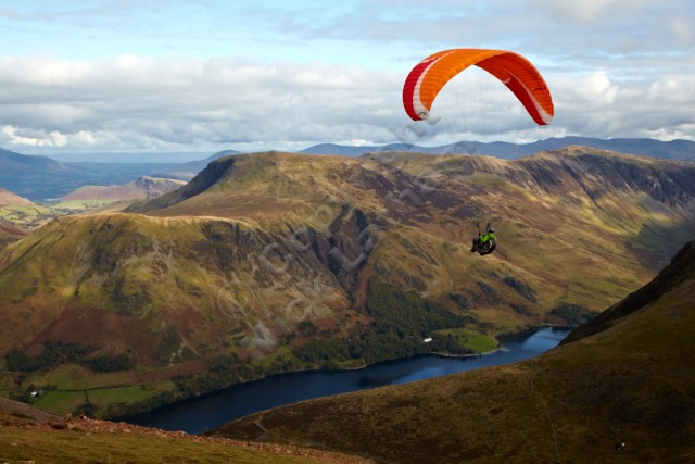 Paraglider soaring over Buttermere valley - looking east from Red Pike