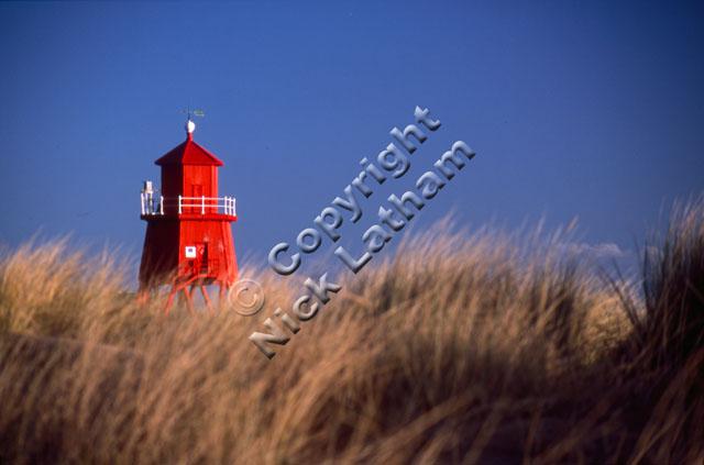 red sand dune grass blue sky tower coast sea