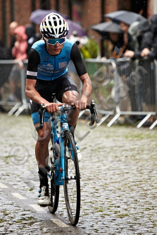 cycling bike hill cobble street steep team competition race winner leader power effort composed controlled spectator